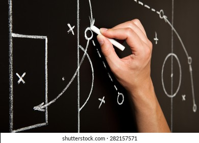 Coach drawing a football game tactics with white chalk on blackboard. Soccer coach explaining game strategy.