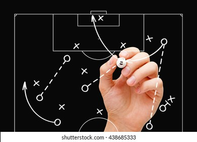 Coach drawing soccer play tactics with white marker on transparent wipe board over black background. Football manager explaining game strategy.