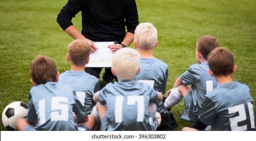 Coach Encouraging Boys Soccer Team. Soccer Football Team with Coach at the Stadium. Coach with Youth Soccer Team. Boys Listen to Coach's Instructions. Coach Giving Team Talk
