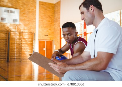 Coach explaining to basketball player while sitting on bench in court