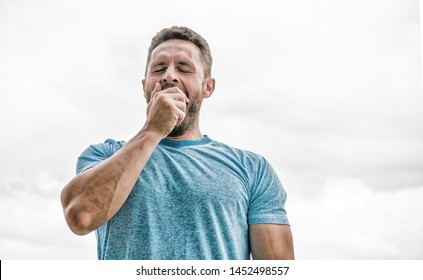 coach in fitness gym. after workout. man athlete in blue sport tshirt. sportswear fashion. yawning muscular male with beard. sleepy man isolated on white. sportsman with athletic body. early morning.