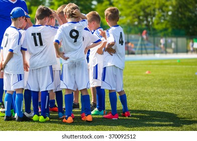 Coach giving young soccer team instructions. Youth soccer team before final game. Football; soccer; handball; volleyball; match for children. Football soccer game. Soccer football background.