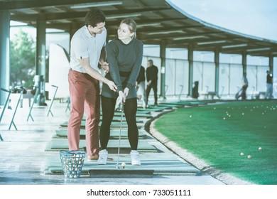 Coach golf shows a young girl right ways strikes a golf ball
