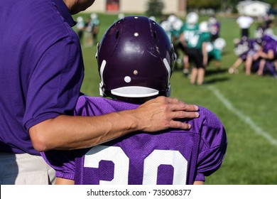 Coach with his arm around his player on the sidelines