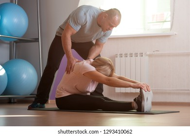 Coach man helps an elderly woman to stretch the body during training in the gym. Healthy lifestyle concept
