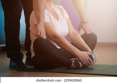 Coach man helps his personal female client woman to stretch the body during training in the gym. Healthy lifestyle concept