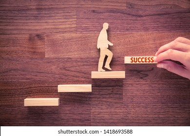 Coach motivate to succeed. Hand with the last peace of stair and person made from wood and wooden stairs, the last with text success.