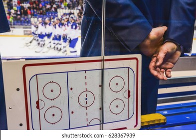 coach on the ice hockey bench with tactic board looking at player after hockey match.