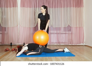 Coach pressing ball on woman back inclined forward and stretching legs. Horizontal shot