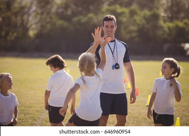 Coach and schoolgirl giving high five to each other during competition in park