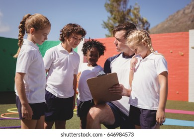 Coach and schoolkids discussing on clipboard in schoolyard