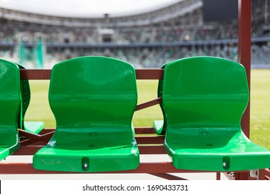 Coach and staff bench, green plastic seats at football stadium