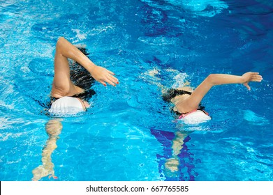Coach with a student swim in the pool with a crawl