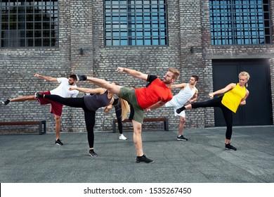Coach teaching his group if trainees about leg kicks, side kick