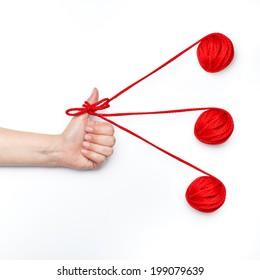 coaching and mentoring personal growth goals conceptual photo with one hand thumb up tangled with red ribbon and three balls