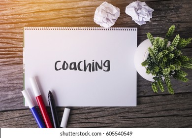 Coaching word with Notepad and green plant on wooden background