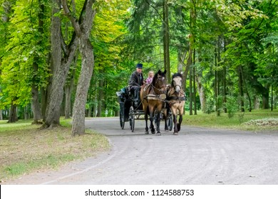 A coachman on horseback drives children in the park of a castle in N vezha on the eve of the 4th of July