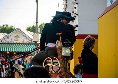 Coachman welcoming a family to the Spring Fair in Seville. May 5, 2019. Seville, Spain.