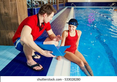 Coach,tranier to swimmer girl at the pool discussing with athlet