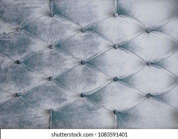 Coach-type velours screed tightened with buttons. Gray chesterfield style quilted upholstery backdrop close up. Capitone pattern texture background