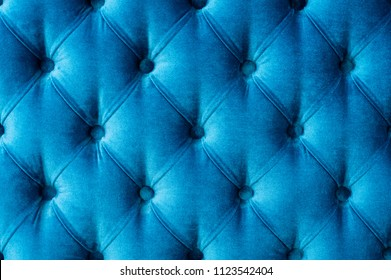 Coach-type velours screed tightened with buttons. Blue chesterfield style quilted upholstery backdrop close up. Capitone pattern texture background