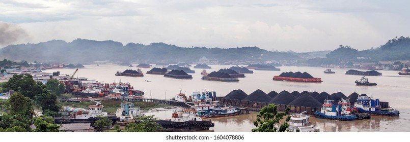 Coal barges floating over Mahakam River in Samarinda, East Kalimantan at December 26th 2019, waiting to cross under the bridge.