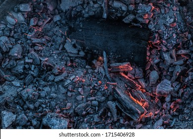 Coal in a blazing fire. Black coal after the fire. Bright flashes on fire.