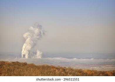 Coal burning plumes over rural landscape