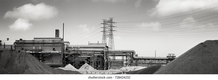 Coal, factory, power lines, partly cloudy sky.