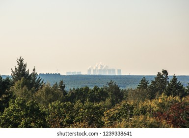 Coal fired power plant smokestacks over vast forest