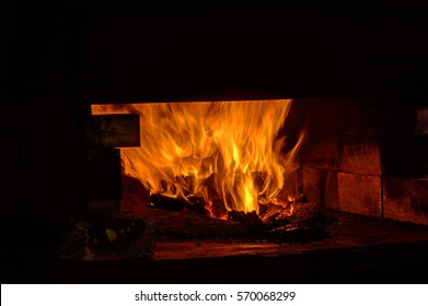 A coal forge in the blacksmith shop blazes and dances