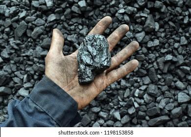 Kohle in der Hand des Arbeitnehmers Bergarbeiter. Bild kann verwendet werden, um Ideen über Kohlebergbau, Energiequelle oder Umweltschutz.