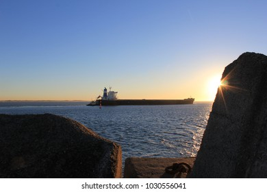 Coal loaded ships leaving Newcastle Harbour for overseas markets with beautiful evening sky and sunsets over water