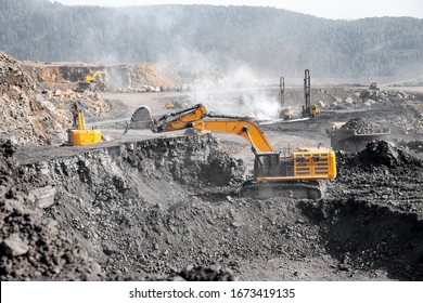 Coal loading at open mining site yellow truck industry.