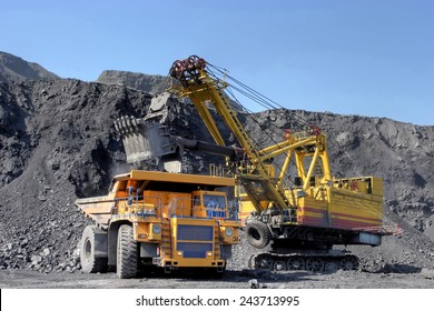 Coal mining. The dredge loads the truck coal.