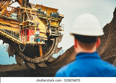 Coal mining in an open pit. Miner looking on the huge excavator. Industry in the Czech Republic, Europe