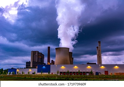 Coal Power plant in cloudy weather. Smoke coming out of one of the cooling towers.