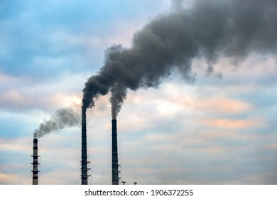Coal power plant high pipes with black smoke moving up polluting atmosphere.