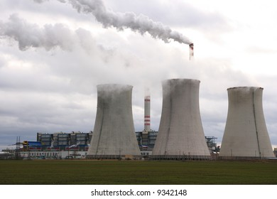 Coal power plant polluting the planet, several thin and several thick chimneys smoking towards the sky.