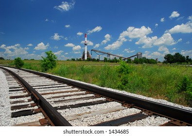 Coal Power Plant and Railroad Tracks, Green Grass, Blue Sky, and Clouds