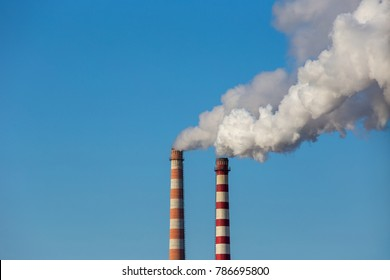 Coal power plant smokestacks emit carbon dioxide pollution by factory under blue sky.