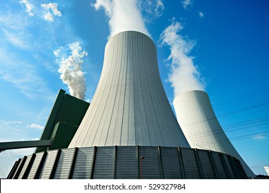 Coal Power Plant smoking and steaming against blue sky