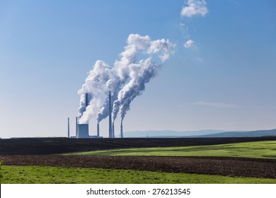 Coal power plant with vapors and smoke against blue sky