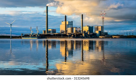 Coal power plant at water front with reflection