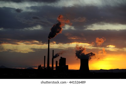 Coal power station in sunset with cloudy sky, industrial landscape