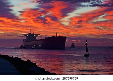 Coal ship entering Newcastle harbour  at sunrise