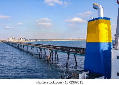 Coal ship funnel with a long industrial pier and a Coal and Gas fired power station including a Flue-Gas chimney in the background.