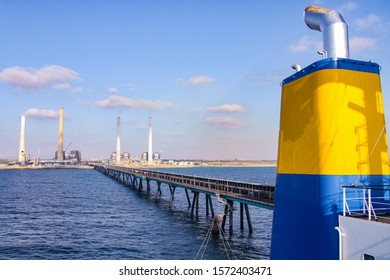 Coal ship funnel with a long industrial pier, sea and blue sky background.