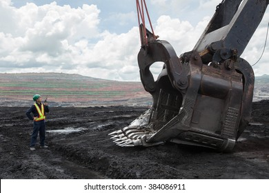 Coal trucks and loaders are hauling the coal away to to a power plant simultaneously.