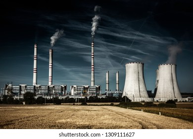A coal-fired power station in the distance in agricultural landscape,cloudy dramatic sky